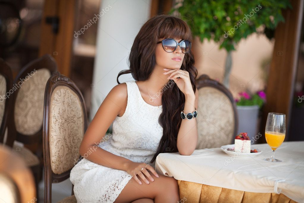 Beautiful Woman at cafe eating cheesecake dessert and drinking juice.