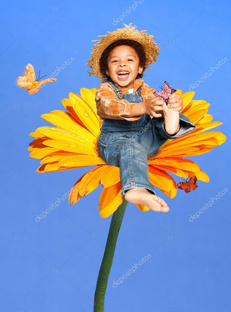 Child sitting on a huge flower playing with butterflies laughing