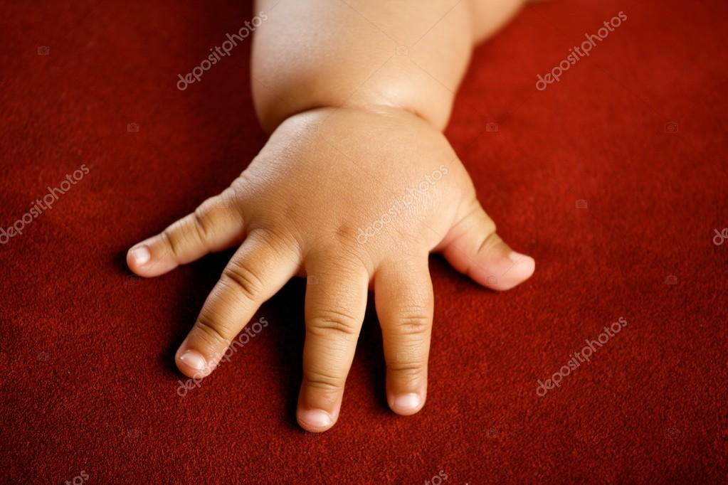 Children's hand isolated on red background