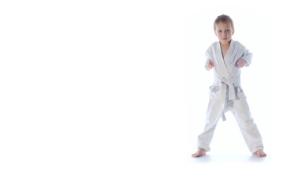 Karate fiú gyakorlása elszigetelt fehér háttér
