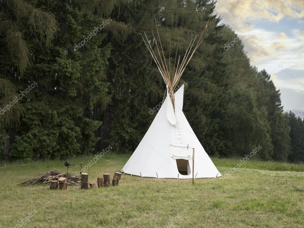Indian american wigwam on the meadow near forest