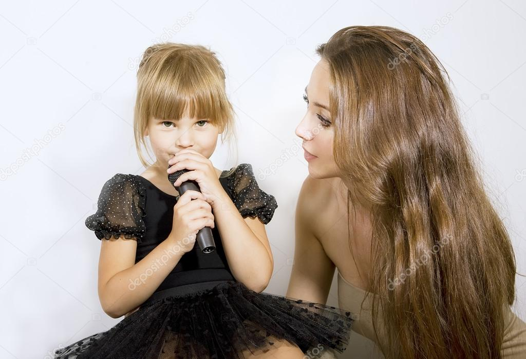 Little girl singing in microphone - mother and girl with a micro