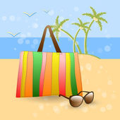 Summer at the beach - stylish accessories on golden sand at the beach: colorful bag and sunglasses.