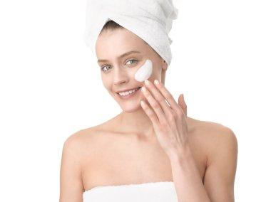 Woman applying moisturizer cream on face. Close-up fresh woman f