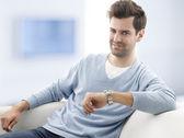 Fotografie mladý muž sedí na pohovce