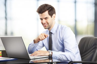 Happy young businessman using laptop in his office