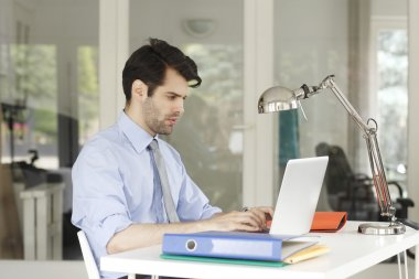 Businessman at office working on laptop