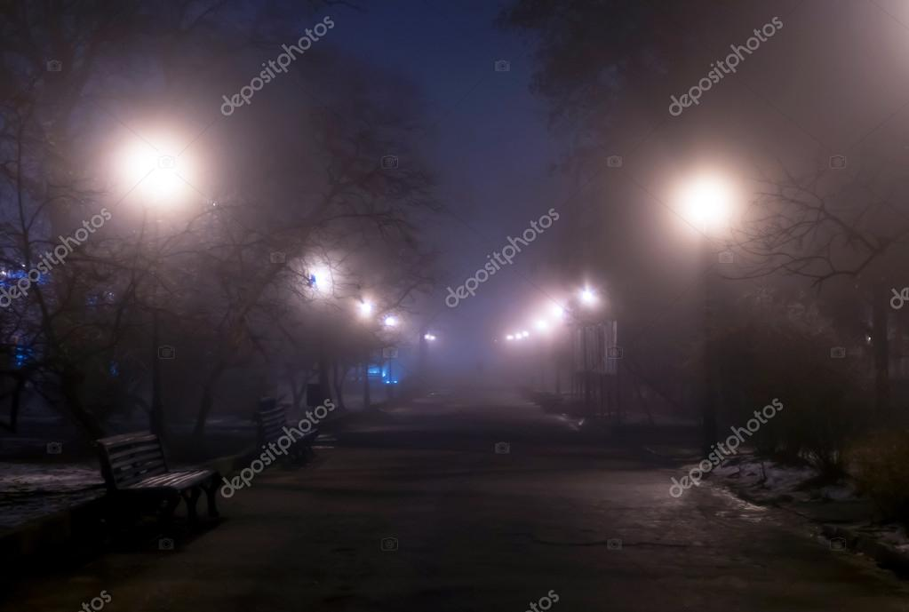 Foggy night park with man's silhouette in the distance.