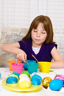 Young girl in the process of coloring Easter eggs has an egg on the spoon completely submerged in dye