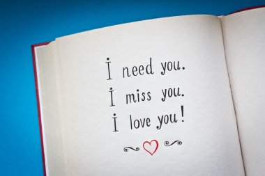 Hand drawn words I need you, I miss you, I love you in the open book with color background