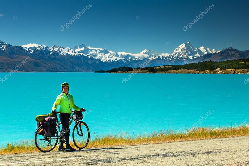 Cyclist stands on mountain road