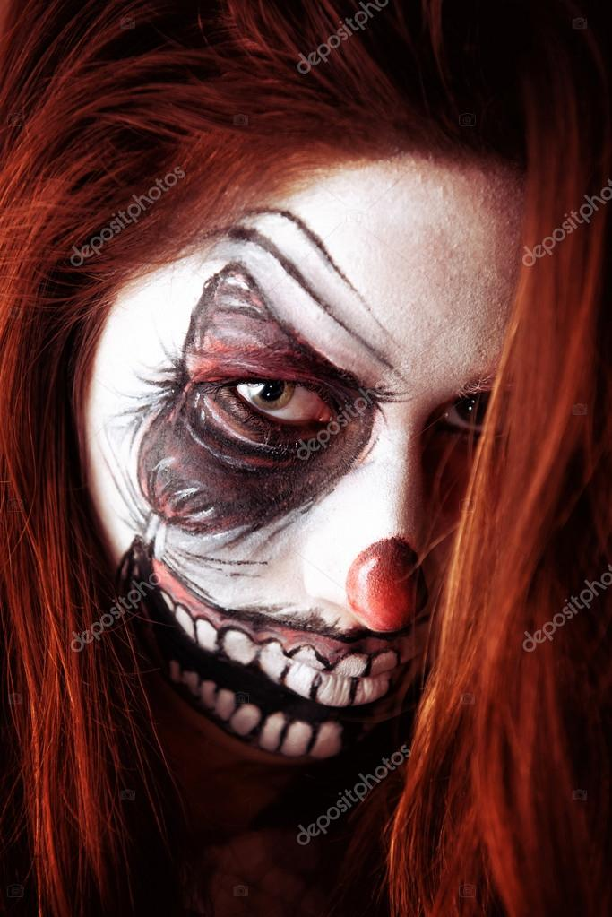 girl with scary clown face painting stock photo