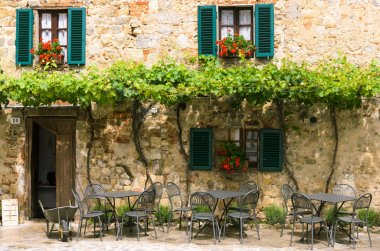 Cafe tables and chairs outside a stone building in Tuscany, Italy stock vector
