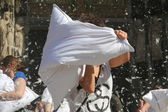 Pillow fight, woman striking out with white cushion