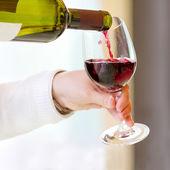 číšník nalil červené víno