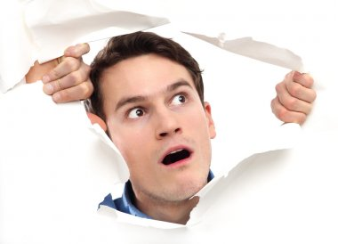 man looking through paper hole