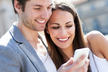 Smiling couple with mobile phone