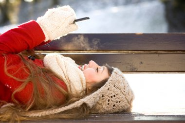 Woman lying on bench with mobile phone