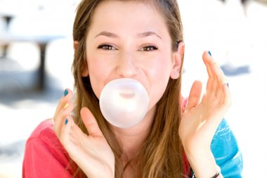 Young girl blowing bubble gum
