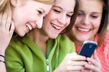 Three Female Friends Laughing and Looking at Cell Phone