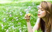 nádherná mladá dívka foukání mýdlové bubliny v parku.