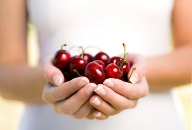 Hands full of cherries