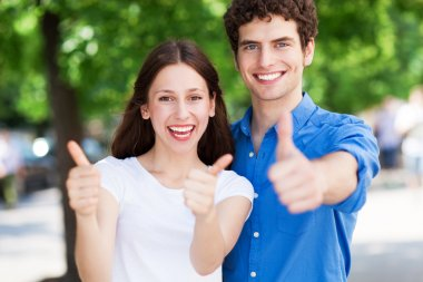 Teenage couple with thumbs up