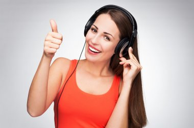 Woman with headphones showing thumbs up