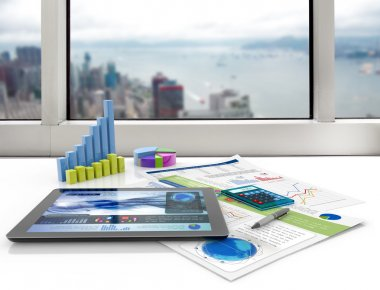 Tablet and financial graphs on a white desk