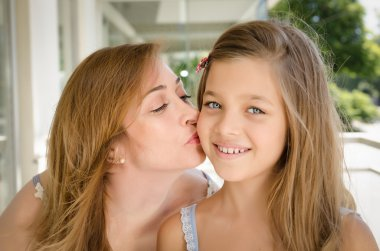 mother kissing daughter in the cheek