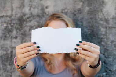 Teenage girl holding sheet of paper