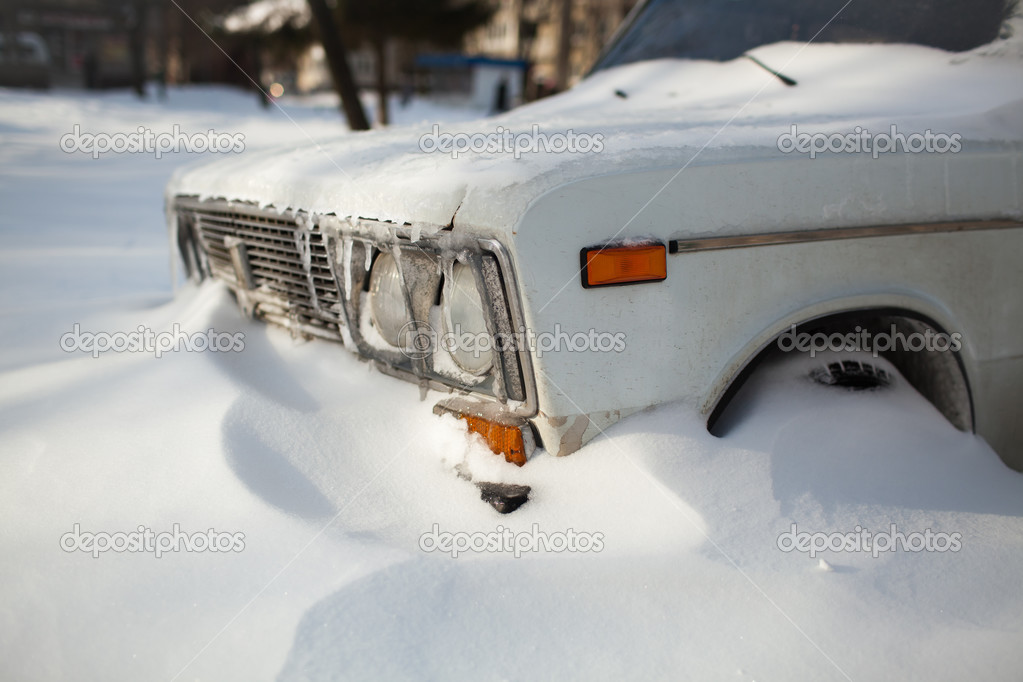 White old car covered with snow
