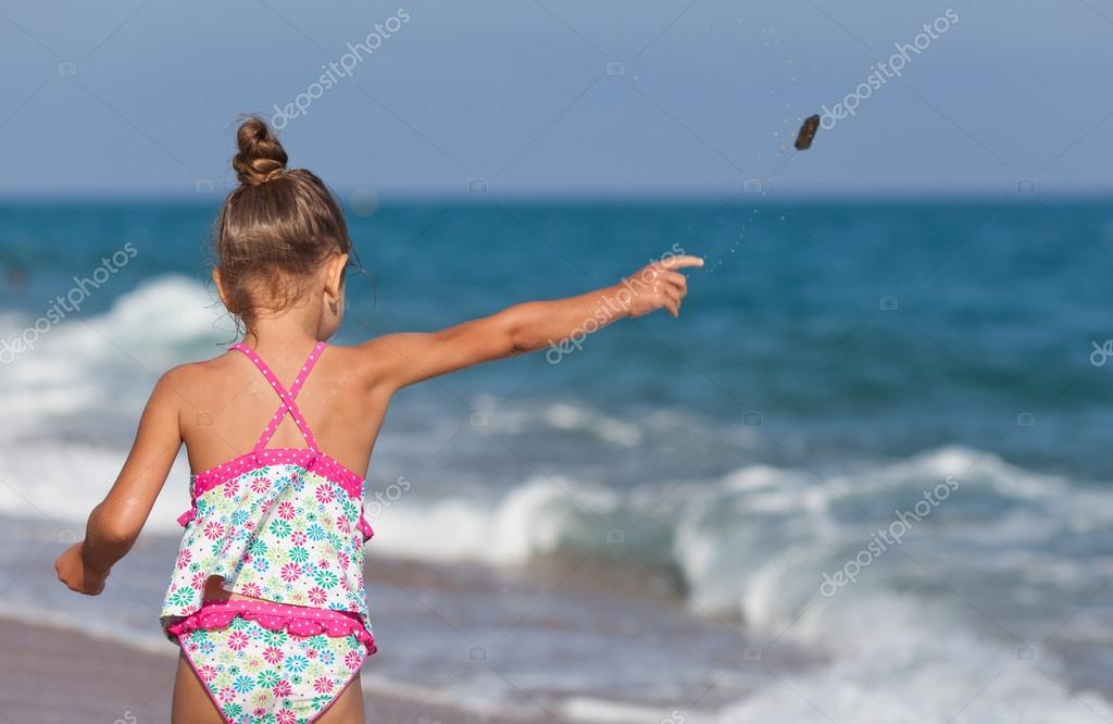 Little girl throws rocks into the sea