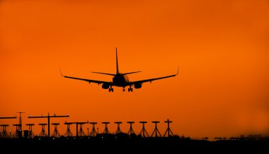 Silhouette of an airplane lands.