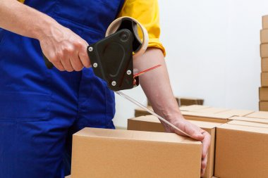 Closeup of a worker hands packing a box stock vector