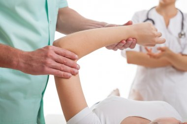 Doctors examining injured arm