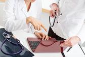 Fotografie Doctors analysing computer documents