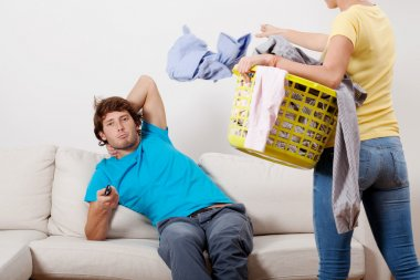Woman cleaning man chilling