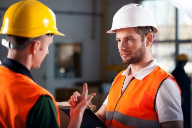 Warehouse workers consulting