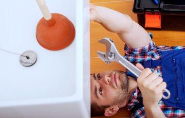 Handy man repairing sink in bathroom