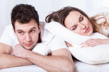 Sleeping wife and thoughtful husband