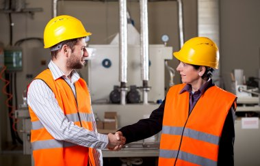Workers in factory shake hands