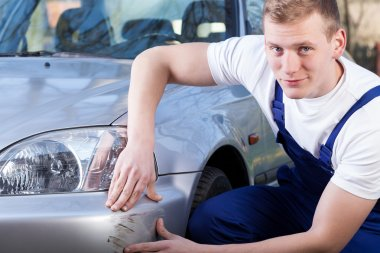 Mechanic repairing car scratching