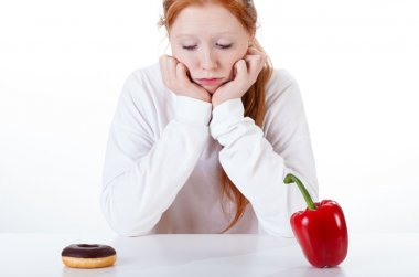 Girl choosing between doughnut and red peppers