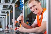 mladý usmívající se muž pracující na výrobní lince