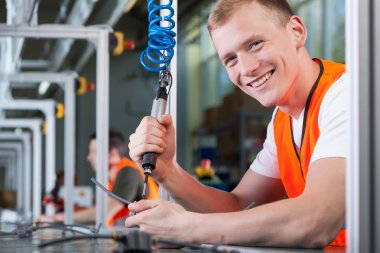 Close-up of a young smiling man working on the production line stock vector
