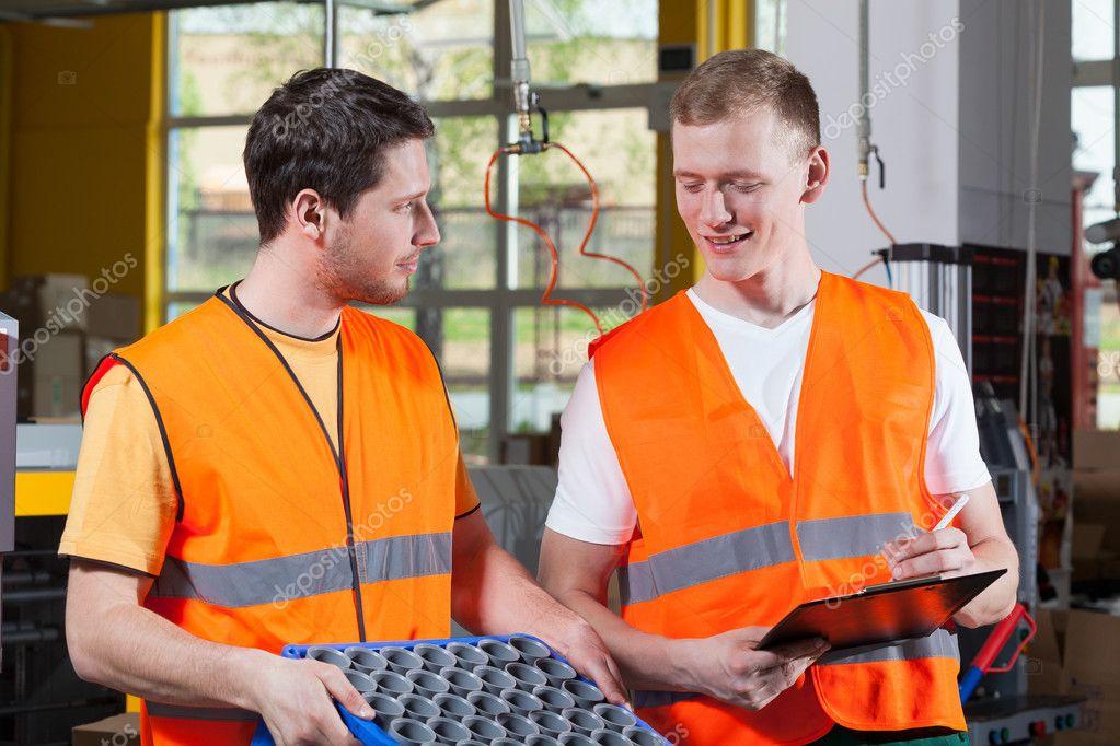 Factory workers in orange protective vest
