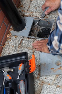 Male hands cleaning pavement drain hole