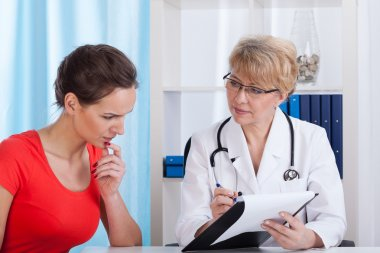 Mature Lady doctor shows a patient test results