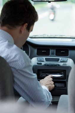 Man changing song in car